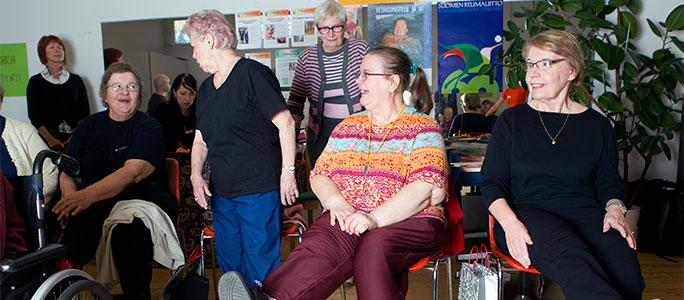 Vanhukset verryttelevät tuoleilla ja nauravat.